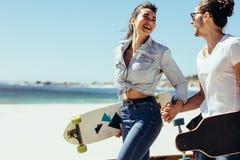 Усмехаясь пары совместно на пляже с скейтбордами Стоковая Фотография