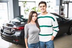 Усмехаясь пары стоя перед автомобилем на новом выставочном зале автомобиля Стоковое фото RF