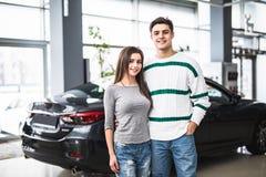 Усмехаясь пары стоя перед автомобилем на новом выставочном зале автомобиля Стоковые Изображения