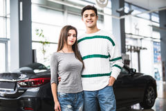 Усмехаясь пары стоя перед автомобилем на новом выставочном зале автомобиля Стоковая Фотография
