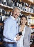 Усмехаясь пары с бутылкой вина в магазине Стоковые Фото