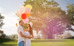 Усмехаясь пары с воздушными шарами outdoors Стоковое Изображение RF