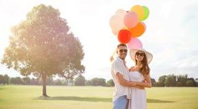Усмехаясь пары с воздушными шарами outdoors Стоковое фото RF