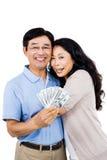 Усмехаясь пары с денежными средствами в кассе стоковые изображения