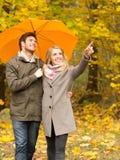 Усмехаясь пары с зонтиком в парке осени Стоковое фото RF