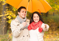 Усмехаясь пары с зонтиком в парке осени Стоковая Фотография RF