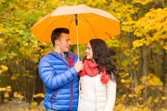 Усмехаясь пары с зонтиком в парке осени Стоковое Фото