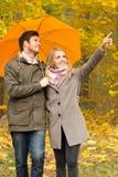 Усмехаясь пары с зонтиком в парке осени Стоковые Изображения