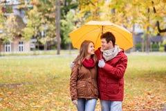 Усмехаясь пары с зонтиком в парке осени Стоковые Фотографии RF