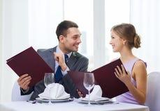 Усмехаясь пары с меню на ресторане Стоковая Фотография