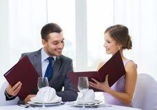 Усмехаясь пары с меню на ресторане Стоковые Фото