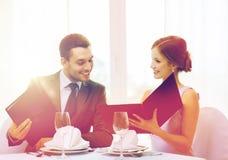 Усмехаясь пары с меню на ресторане Стоковые Изображения RF