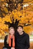 Усмехаясь пары с оранжевым портретом кленовых листов осени Стоковое Изображение RF