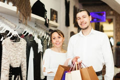 Усмехаясь пары с сумками на бутике одежды Стоковое Фото
