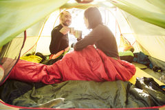 Усмехаясь пары туристов выпивая кофе от кружек в шатре Стоковые Фото