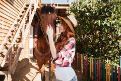 Усмехаясь пастушка женщины позаботить о ее лошадь на ферме Стоковая Фотография