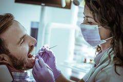 Усмехаясь пациент дантиста рассматривая усмехаясь Стоковое фото RF