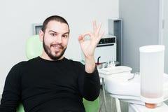 Усмехаясь пациент на показе дантиста одобряет или улучшает жест Стоковые Фотографии RF