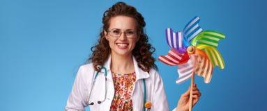 Усмехаясь педиатр врачует показывать красочную ветрянку на сини Стоковые Изображения RF