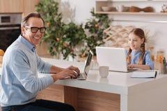 Усмехаясь пенсионер и ребенк используя современные компьтер-книжки дома Стоковое Изображение