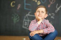 Усмехаясь первый грейдер сидит на предпосылке школьного правления стоковые изображения rf