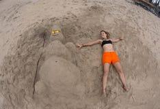 Усмехаясь песочный снеговик в красной шляпе santa на море Стоковые Фотографии RF