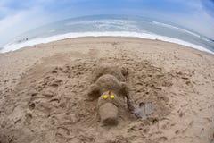 Усмехаясь песочный снеговик в красной шляпе santa на море Стоковое Изображение RF