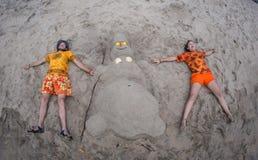 Усмехаясь песочный снеговик в красной шляпе santa на море Стоковые Изображения RF