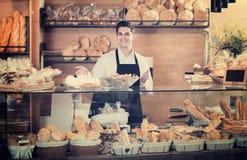 Усмехаясь печенье мужского работника хлебопекарни предлагая Стоковое Фото