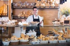Усмехаясь печенье мужского работника хлебопекарни предлагая Стоковые Фото