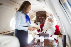 Усмехаясь печенья сервировки стюардессы к Санте внутри Стоковое Фото