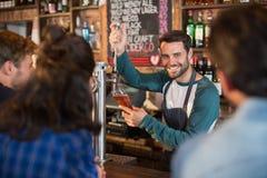 Усмехаясь пиво бармена лить в стекле для клиентов стоковые изображения