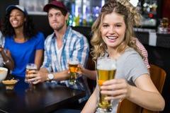 Усмехаясь пиво белокурой женщины предлагая Стоковые Фото