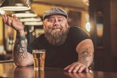 Усмехаясь пиво бородатого мужчины выпивая в пабе Стоковые Изображения RF