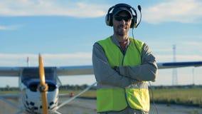 Усмехаясь пилот стоит около самолет-биплана в поле видеоматериал