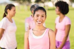 Усмехаясь пинк женщины нося для рака молочной железы перед друзьями Стоковые Фотографии RF