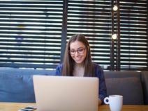 Усмехаясь писатель женщины имея видео- звонок через портативный компьютер, сидя в интерьере кофейни Стоковая Фотография