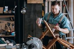 Усмехаясь плотник восстанавливая деревянный стул стоковые изображения