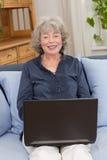 Усмехаясь пожилая женщина с компьтер-книжкой Стоковые Изображения RF