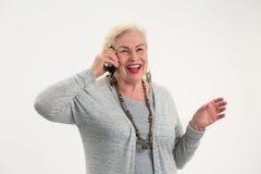 Усмехаясь пожилая женщина с мобильным телефоном Стоковое фото RF