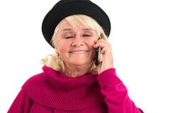 Усмехаясь пожилая женщина с мобильным телефоном Стоковые Изображения RF