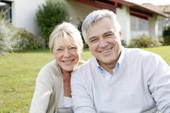 Усмехаясь пожилые пары сидя в домашнем саде стоковая фотография