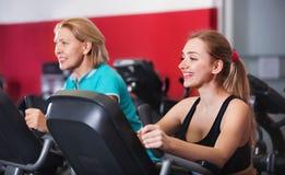Усмехаясь пожилые люди и молодые женщины разрабатывая в спортзале Стоковая Фотография RF