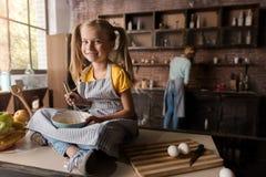 Усмехаясь позабавленные яичка девушки смешивая сидя на таблице Стоковое Изображение
