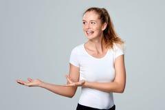 Усмехаясь показ женщины раскрывает ладонь руки с космосом экземпляра стоковые фотографии rf