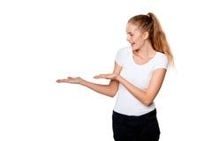 Усмехаясь показ женщины раскрывает ладонь руки с космосом экземпляра стоковая фотография rf