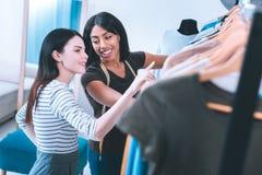 Усмехаясь показ продавца к собранию клиента новому одежд стоковая фотография