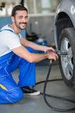 Усмехаясь покрышка механика изменяя на автомобиле Стоковая Фотография