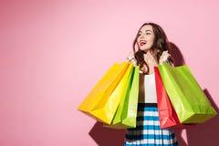 Усмехаясь покупатель молодой женщины держа хозяйственные сумки и смотря прочь Стоковая Фотография RF