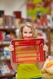 Усмехаясь покупки женщины в супермаркете Гастроном стоковые фото